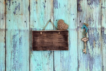 Blank rustic sign with heart and skeleton key hanging on antique teal blue wood background