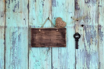 Blank rustic sign with heart and antique key hanging on teal blue wood background