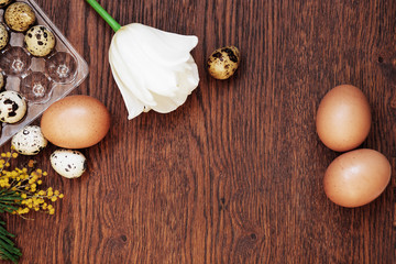 A goose egg, hen egg and a quail egg on a wooden background.