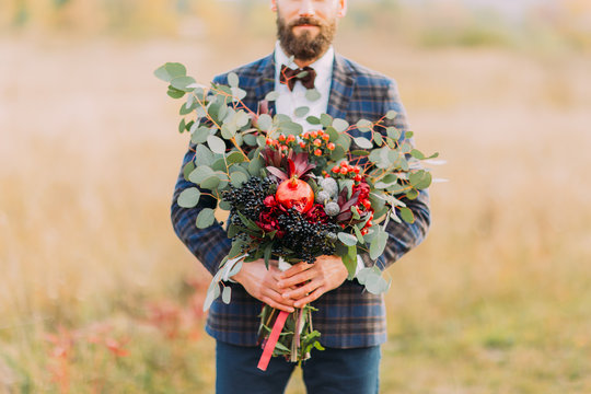 Bearded groom with bouquet of fruits on the field