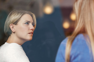 Woman looking concerned while listening carefully to her friend