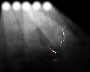 Man playing guitar with spotlight and smoke.