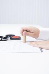 契約書に捺印する女性の手元 縦構図