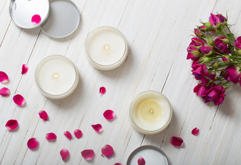 roses with candles on a wooden background