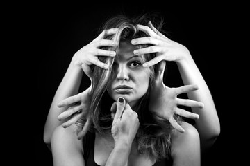 portrait of emotional young woman and lot of hands