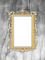 Close-up of golden Baroque picture frame on grey weathered wooden background