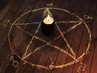 Black candle in pentagram on wooden planks