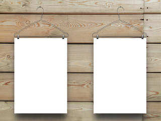 Close-up of two hanged blank frames with clothes hangers on horizontal brown wooden boards background