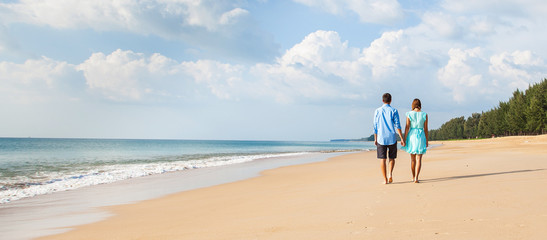 Young happy interracial couple walking on beach .  Banner. Back view.