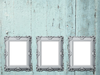 Close-up of three silver Baroque picture frames on weathered aqua wooden background
