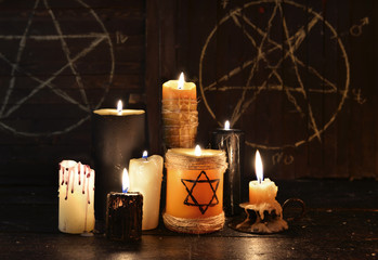 Warlock candles on wooden background with pentagrams