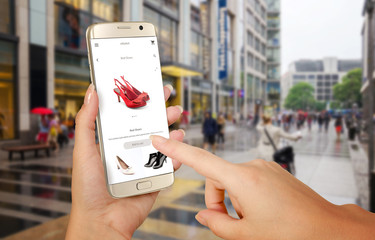 Online shopping with smart phone. Phone in woman hand. Buying women shoes on online store. Street walk and visiting shopping malls.