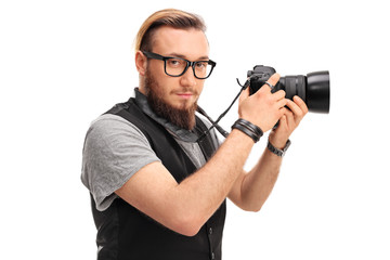 Young male hipster holding a camera