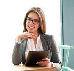 Happy businesswoman sitting  in office with laptop on white