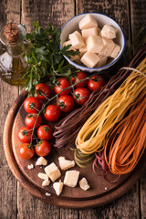 Vegetable color Pasta, oil,tomatoes,cheese on wooden table. italian food