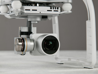 White drone quad copter with 4K digital camera.