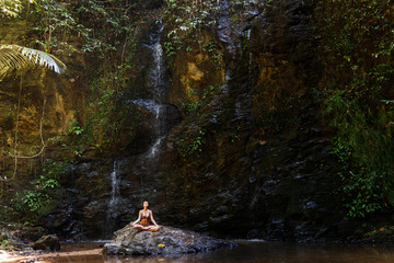 Woman meditating in nature waterfall on the rock