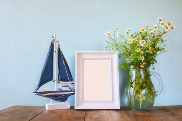 fresh daisy flowers, blank photo frame and wooden boat on wooden table