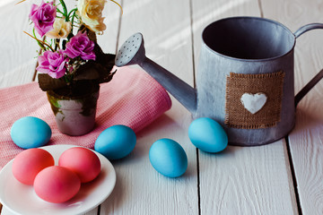 Easter background with blue and pink  Easter eggs and watering can on white wooden background