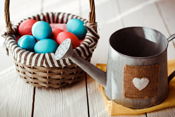 Multicolored Easter eggs in wicker basket on white wooden background