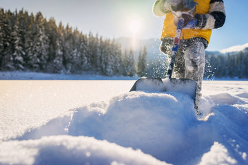 Close-up of a boy shoveling snow