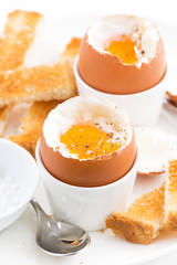 soft boiled eggs and crispy toast for breakfast, vertical