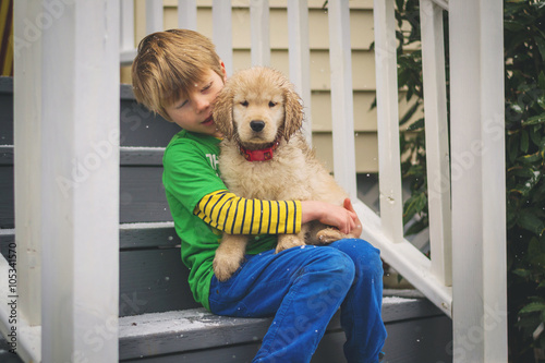Boy Sitting On Couch With Golden Retriever Puppy Dog Stock Photo