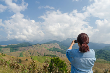 Female traveler with smart phone taking a photo of beautiful landscape at nan thailand