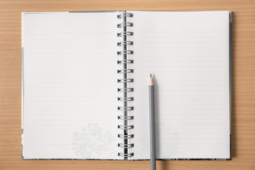 Notebook on the wooden table with pencil