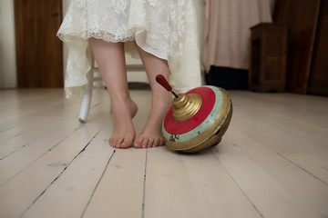 Low section of a woman with spinning top on floor