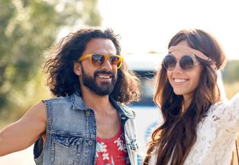 smiling young hippie couple over minivan car