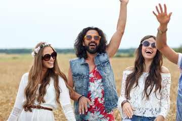 happy young hippie friends dancing on cereal field