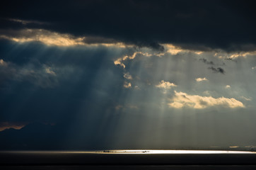 Divine light on a long pier after a sea storm, Sardinia, Italy