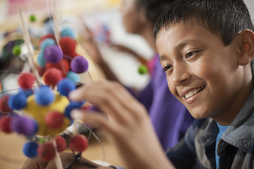 A group of students around a desk in a science lesson, creating molecular models,