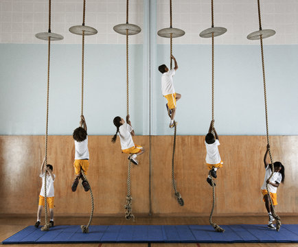 Children climbing ropes in school gym