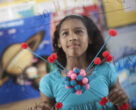 A girl holding a molecular structure and looking at a board of equations and formulae in the classroom,