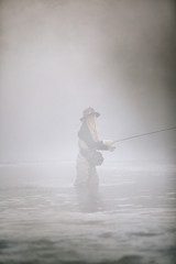 A woman fisherman fly fishing, standing in waders in thigh deep water,
