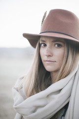 A woman in a wide brimmed hat with a scarf around her neck,