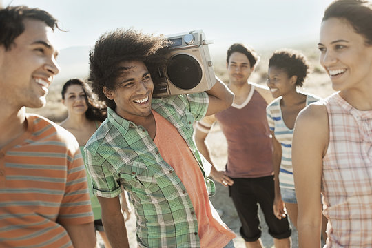 Group of young people, men and women walking on the open road with a boombox,