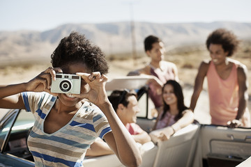 A group of friends by a pale blue convertible on the open road, on a flat plain surrounded by mountains, one holding a camera,