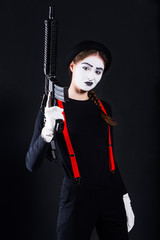 Girl actor in the role of mime holding gun in hands/Mime girl in hat with rifle in hands looking at camera against  black background