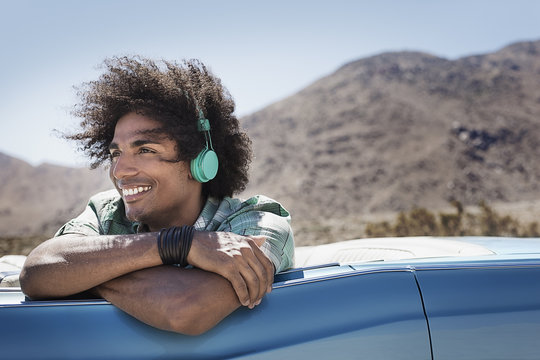 A young man with music headphones sitting in the back of a pale blue convertible on the open road in the mountains,
