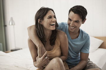 A young couple sitting together on the edge of a bed, laughing and hugging,
