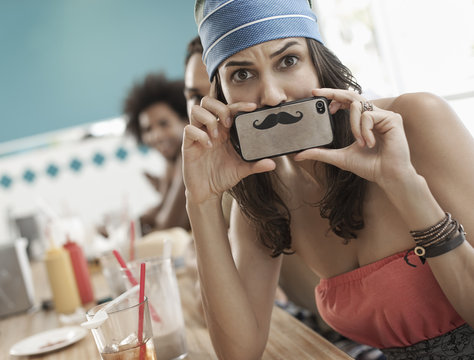 A woman holding a picture of a moustache on her smart phone just under her nose,