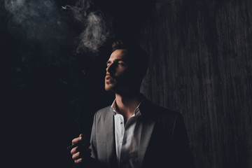 Successful businessman with cigar and smoke on black background