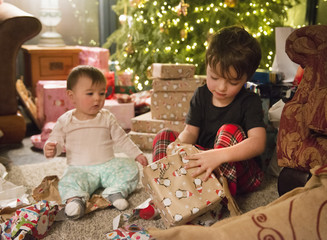 A family at home on Christmas Day, two children sitting among the presents by the tree,