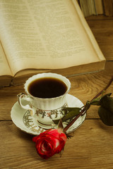 Old books and a cup of coffee with a rose