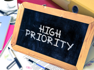 High Priority Handwritten on a Chalkboard. Composition with Small Chalkboard on Background of Working Table with Office Folders, Stationery, Reports. Blurred Background. Toned Image. 3D Render.