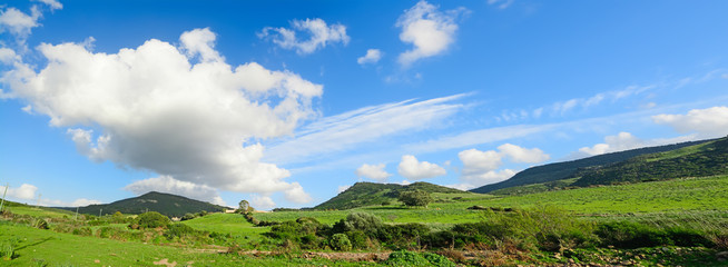 Poster Hill green hills under a blue sky with clouds