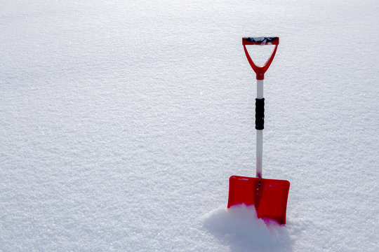 Red snow shovel standing in the snow